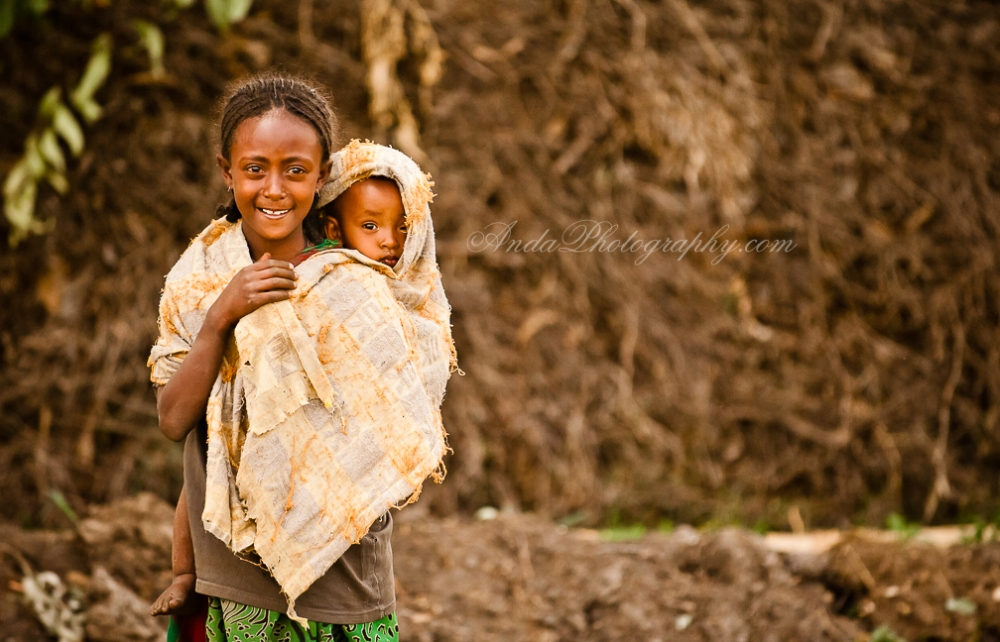 Young Ethiopian girl with her younger sibling on her back